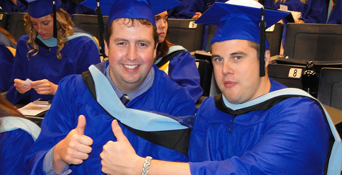 Two graduates give the thumbs up