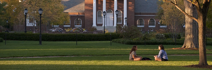 Two students sitting on the green in the fall with Memorial Hall in the background