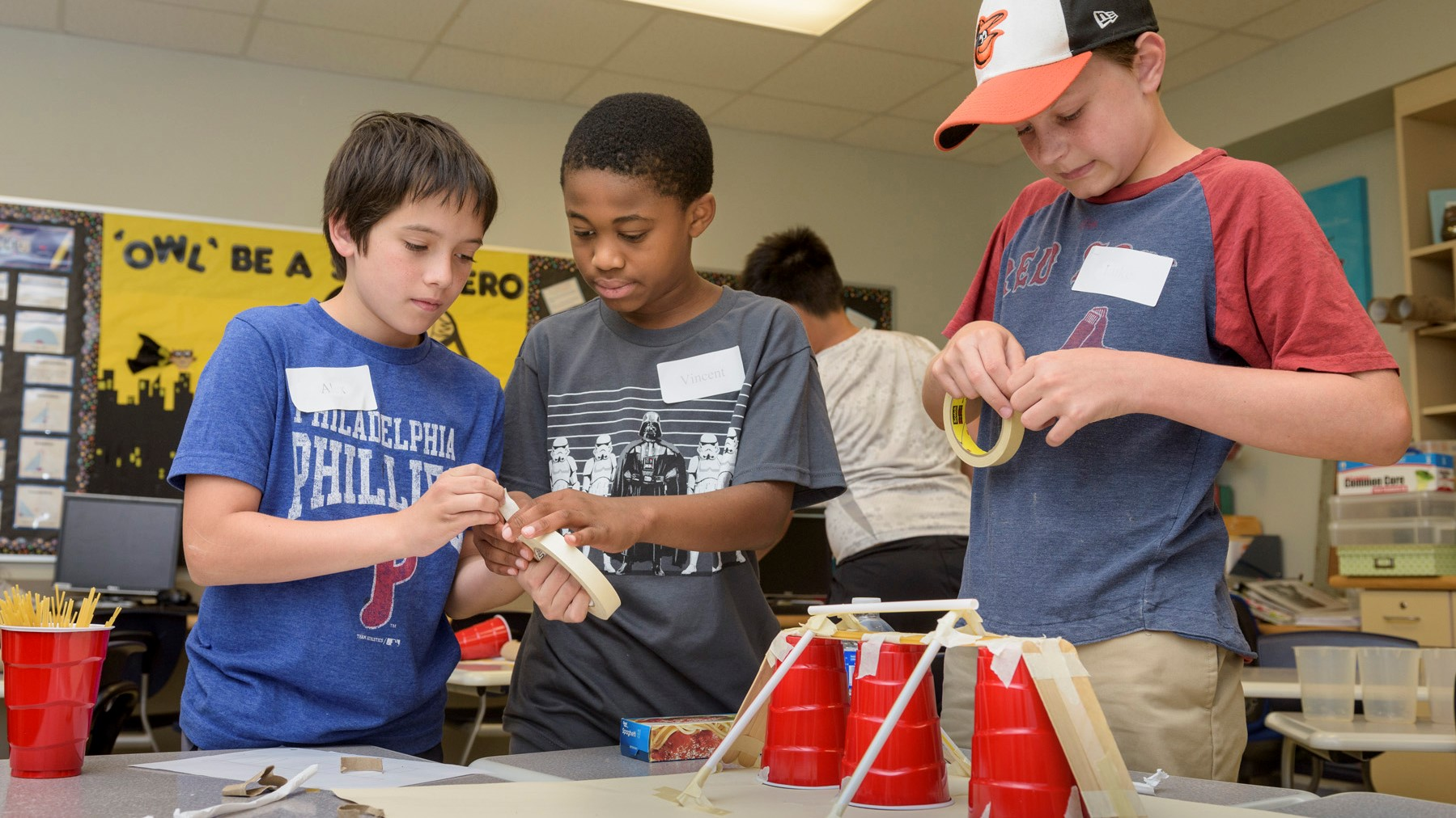 Three middle school boys engage in a STEM activity with plastic cups, spaghetti, and tape in a CEHD summer camp.
