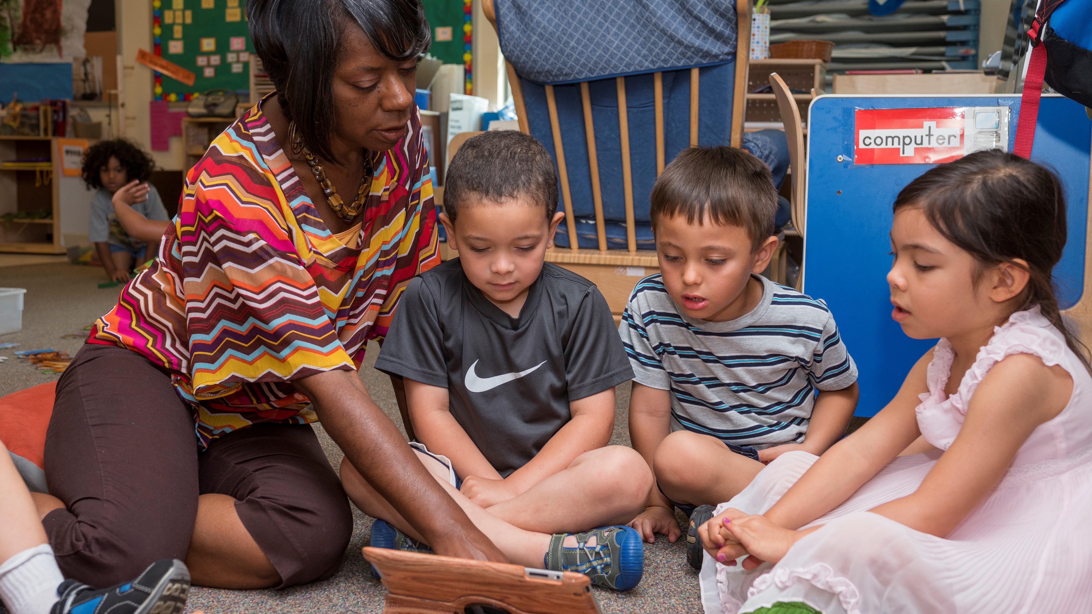 A teacher reads on an iPad with children.