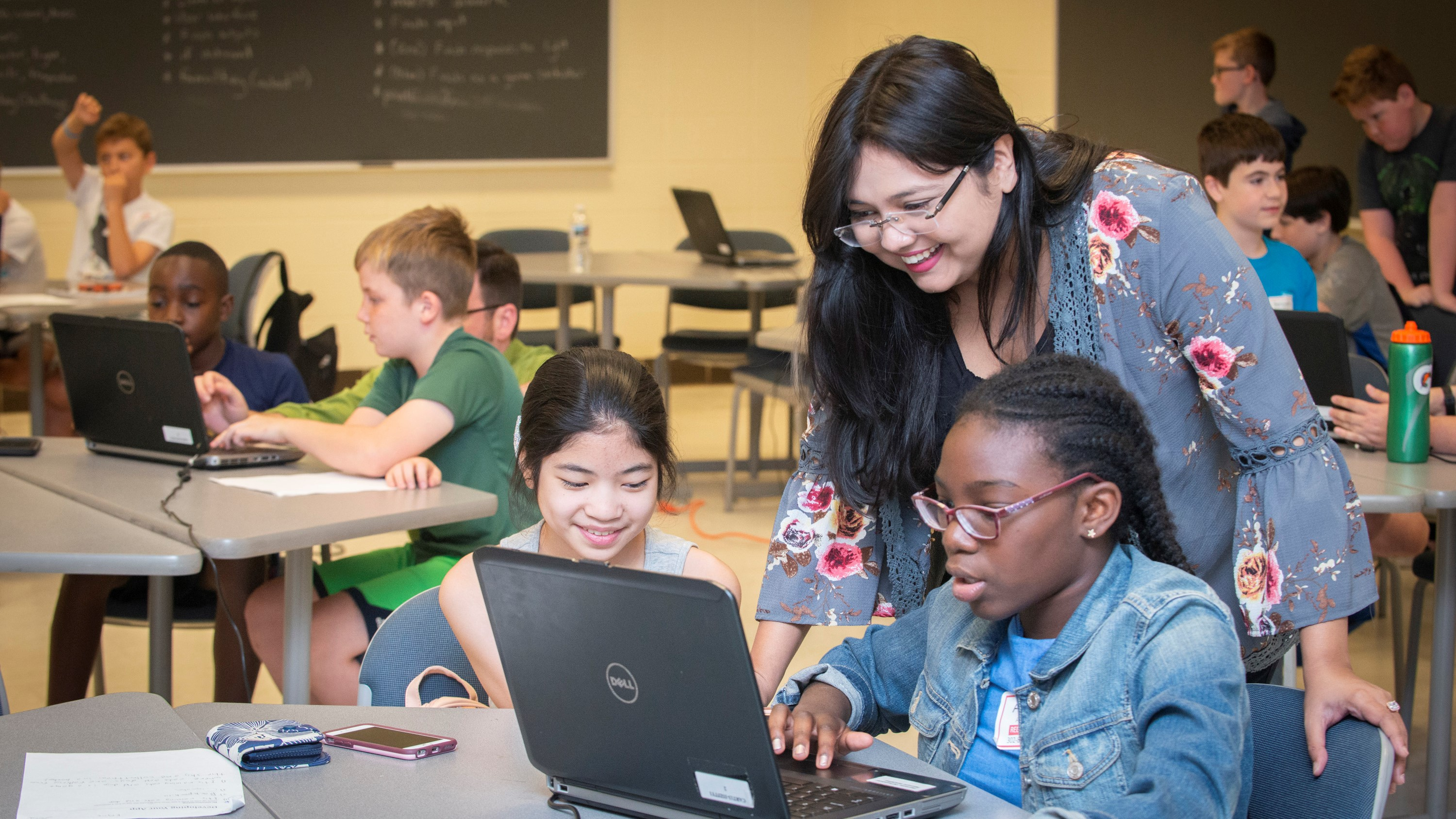 A University of Delaware student works on a computer science activity on a laptop with two middle school students.