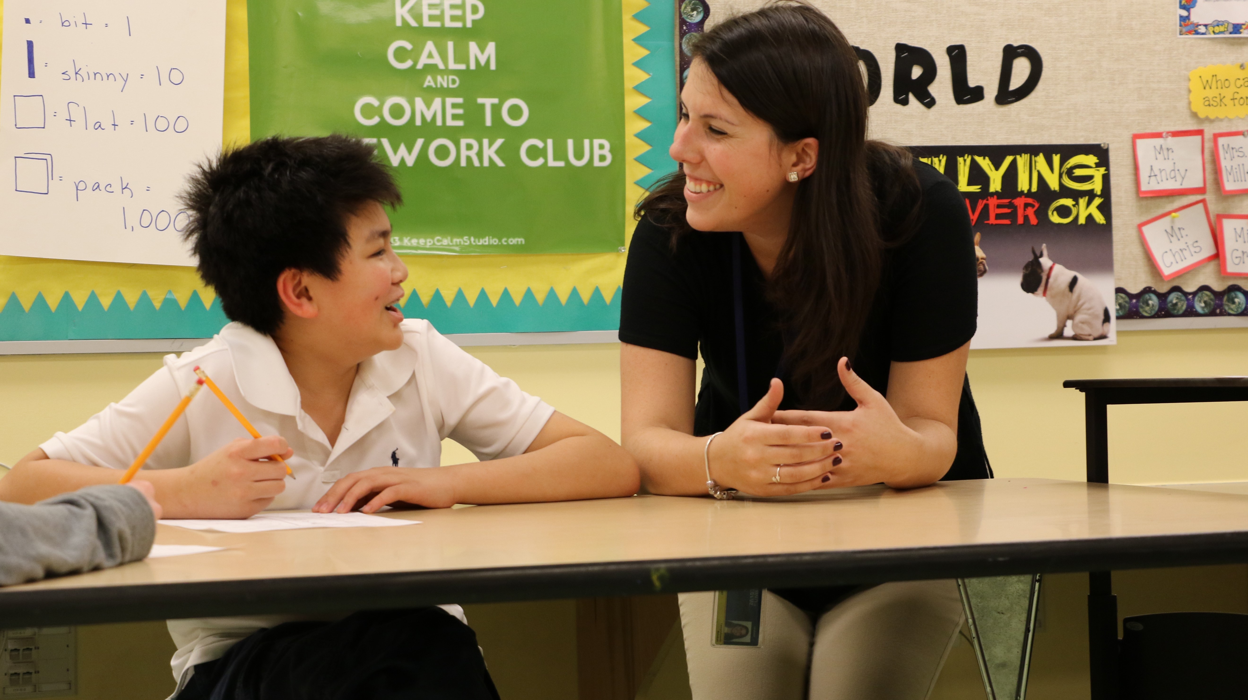 A student in the special education program smiles at a boy in a classroom.