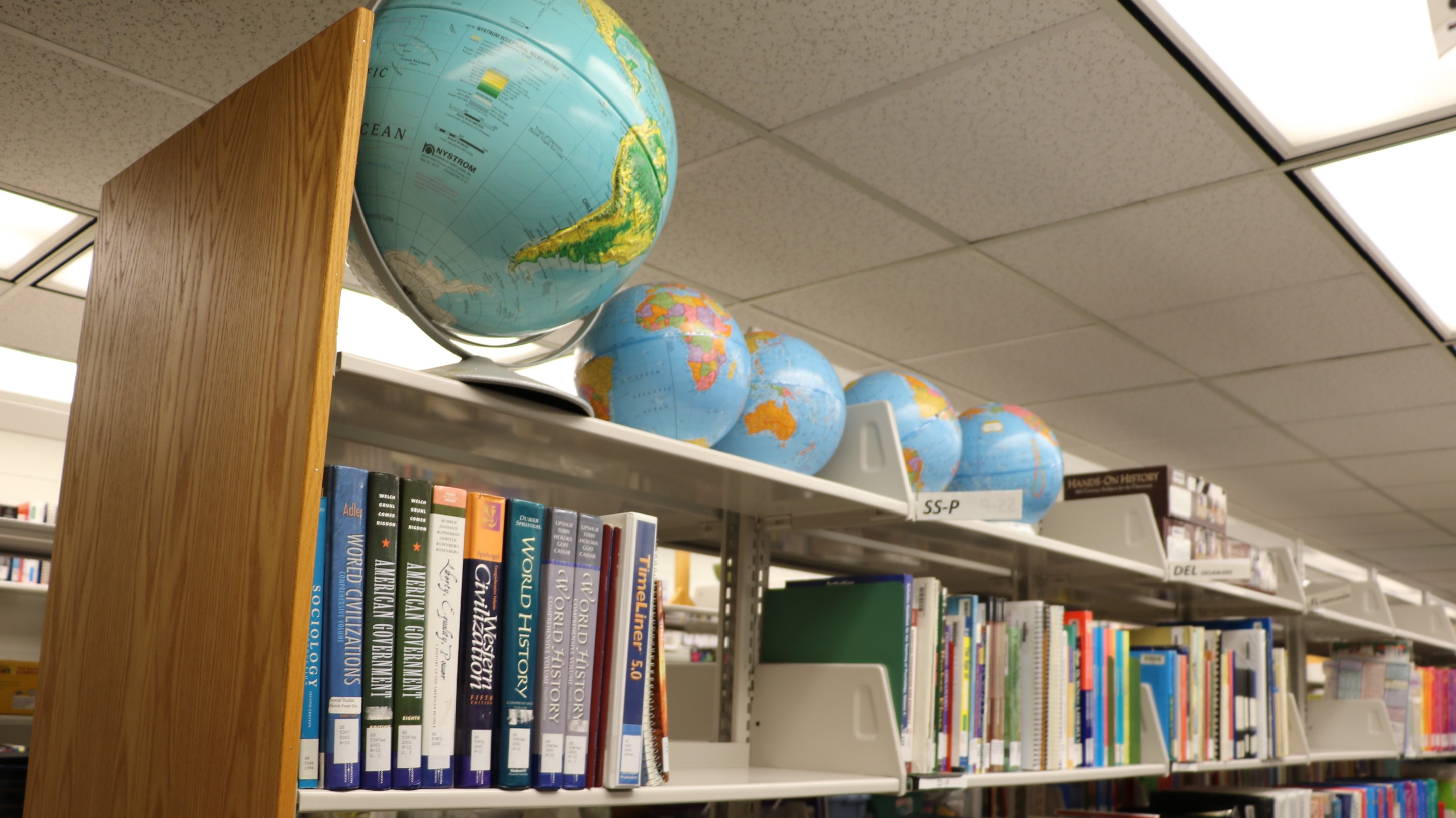 This image shows a row of resources at the Educational Resource Center, which include globes and World History reference books.