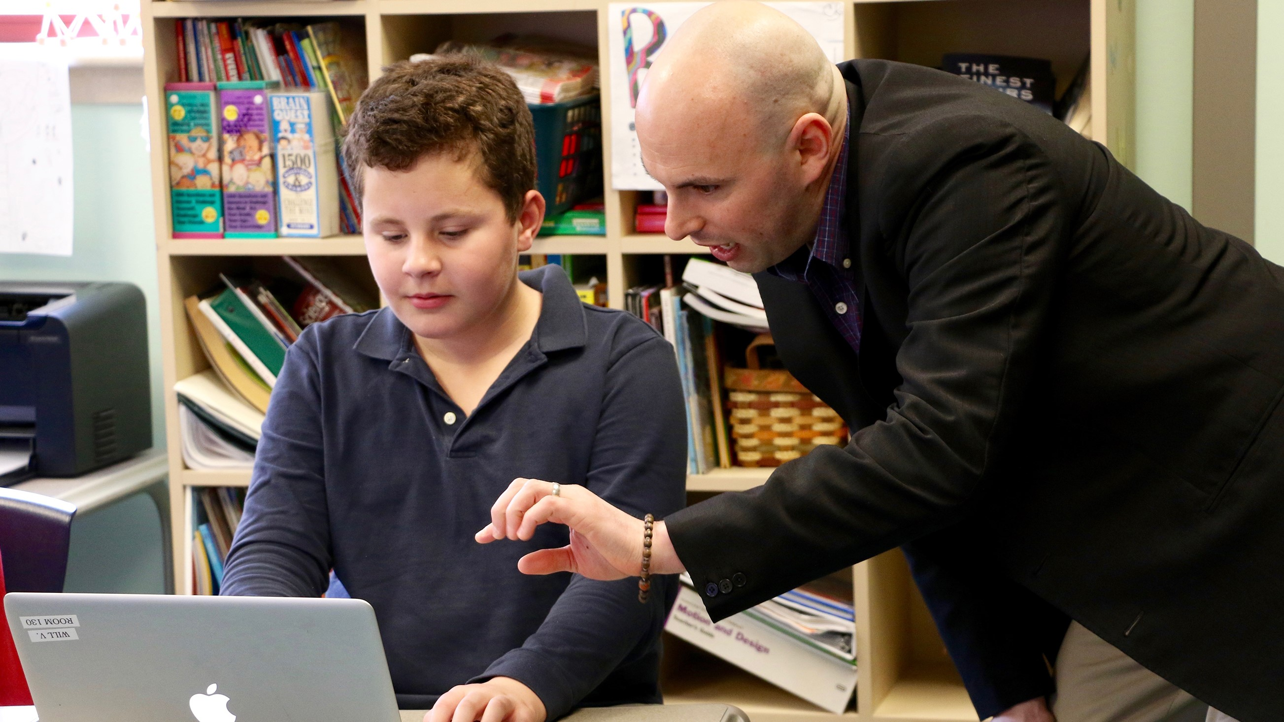 A UD professor works with a child on a classroom activity using laptops on CEHD's Children's Campus.