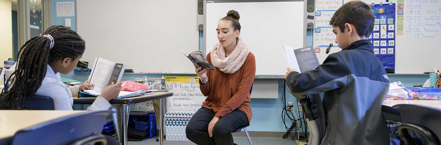 A student teacher reads to students in a classroom as they follow along in their books