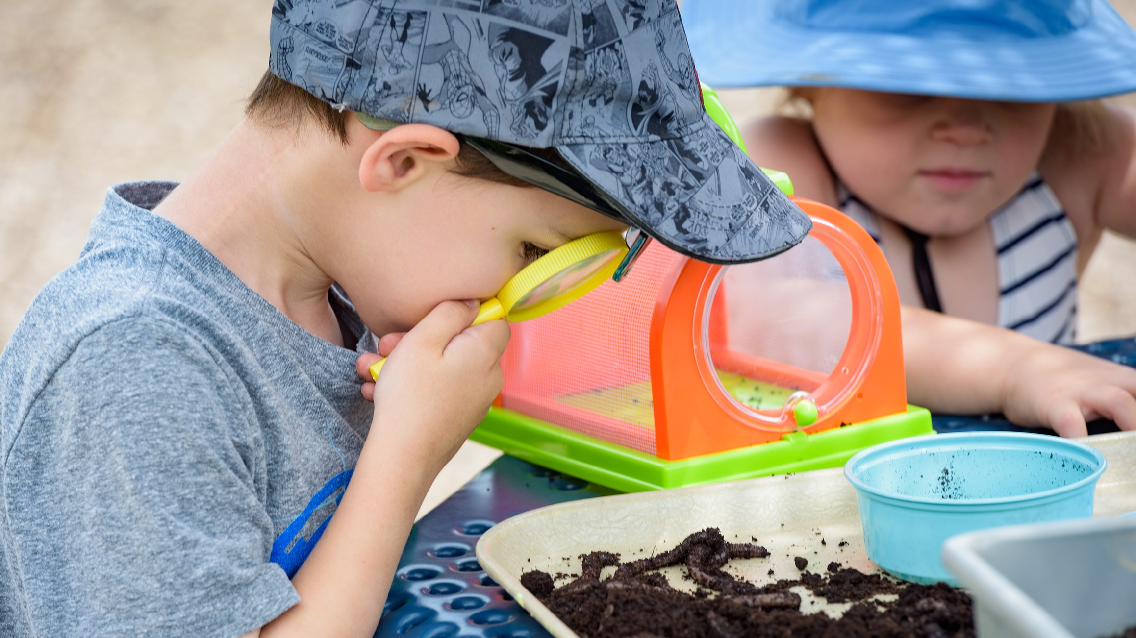 A boy studies earth worms with a magnifying glass during a nature-based activity.