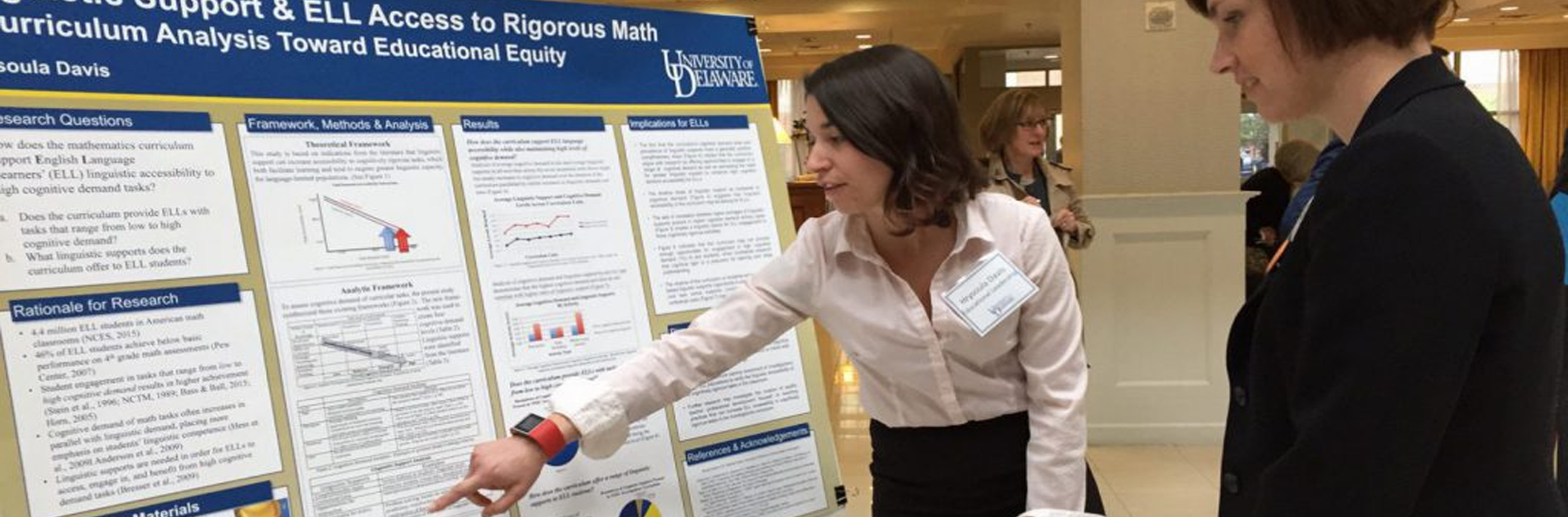 Doctoral student shows her research poster to a woman