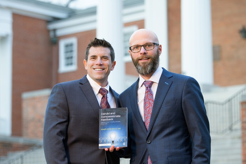 This image shows UD alumni Joseph Jones and T.J. Vari, administrators in the New Castle County Vocational Technical School District and Appoquinimink School District, respectively, with their new book on UD's campus. Their new book, Candid and Compassionate Feedback, is available through Routledge.