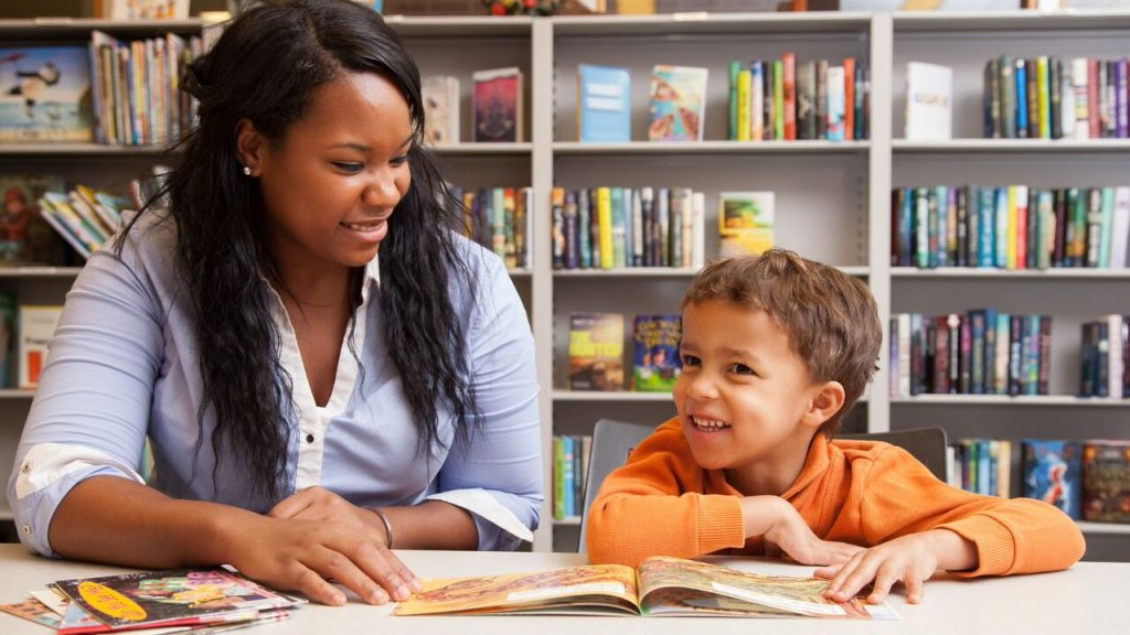 A staff member in UD Center for Research Use in Education reads books with a child in the reading room of UD's Education Resource Center.