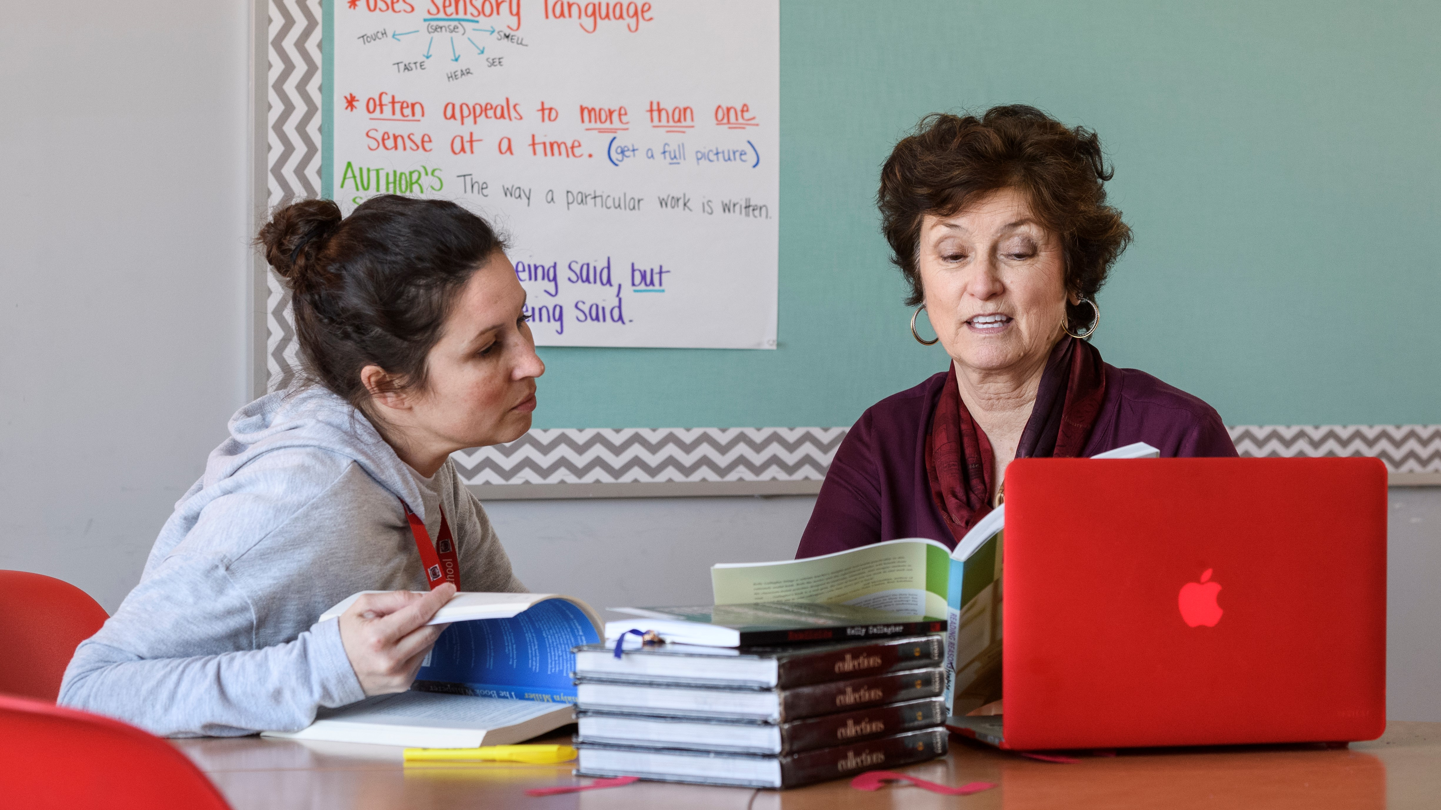 A teacher works with a member of UD's Professional Development Center for Educators at a table in her classroom.