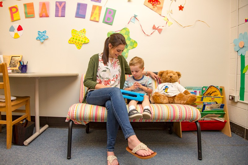 Hillary May, who was crowned Miss Delaware 2019, is a graduate research assistant at the University of Delaware in the Child's Play, Learning, and Development Lab, where she studies how toddlers develop language skills. She plays with a child on a couch in UD's Child's Play, Learning and Development Lab.