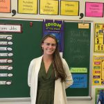 Elementary teacher education alumna poses for a photo in her elementary classroom.
