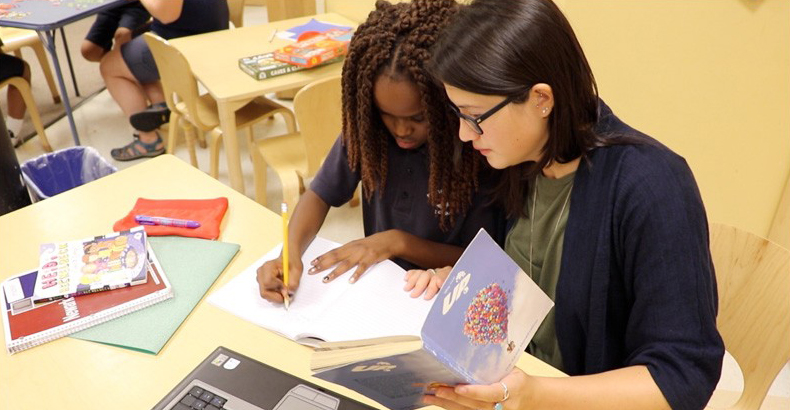 Two students work together on a literacy assignment in classroom with books, paper and pencil, and a computer.