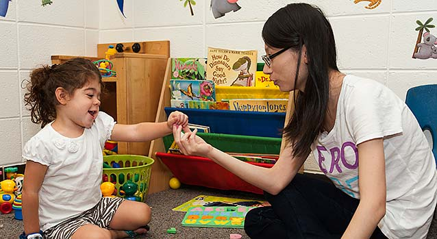 Doctoral student engages in research activity with a child