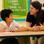 A doctoral student smiles at a boy in a classroom