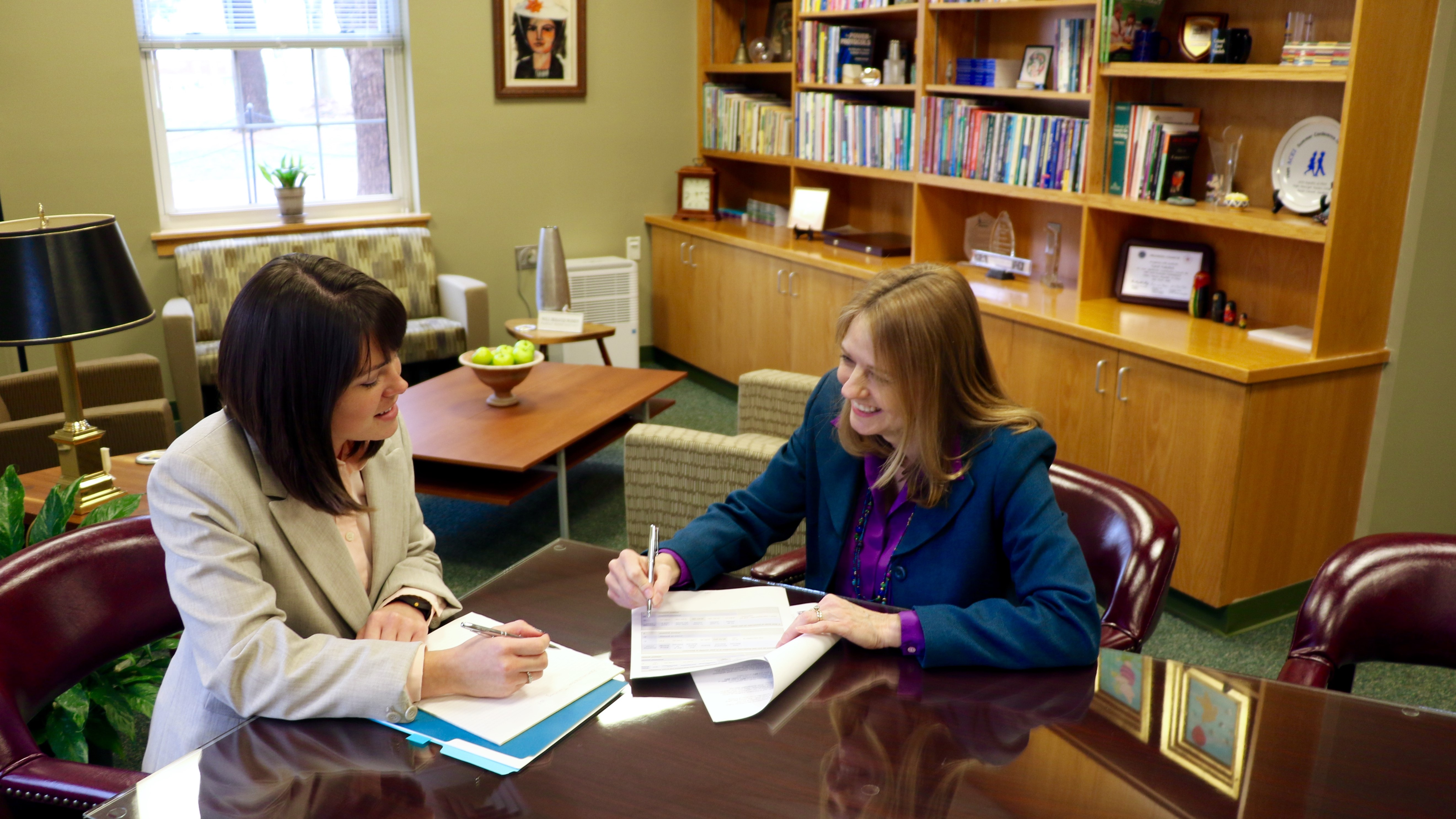 A CEHD advisor meets with a student in her office to discuss program offerings and course schedules.