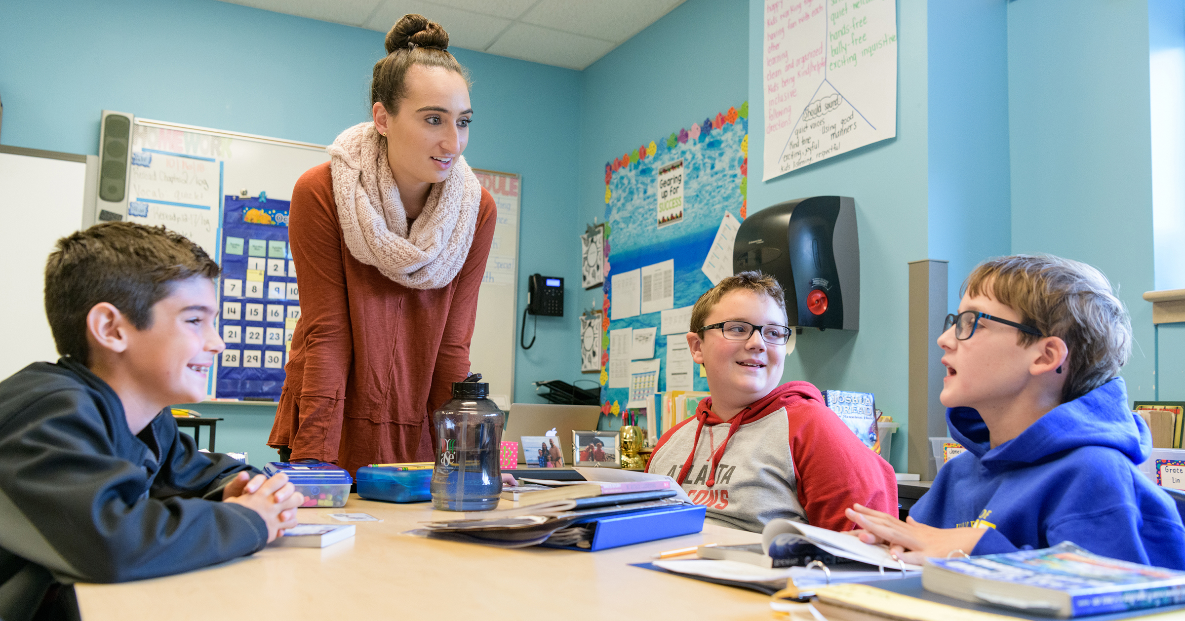A student teacher in UD's ETE program works with children around a classroom table on CEHD's Children's Campus.