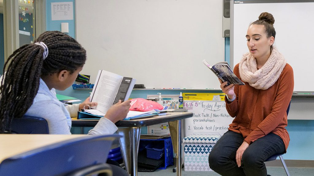 A student teacher reads to students in a classroom as they follow along in their books.