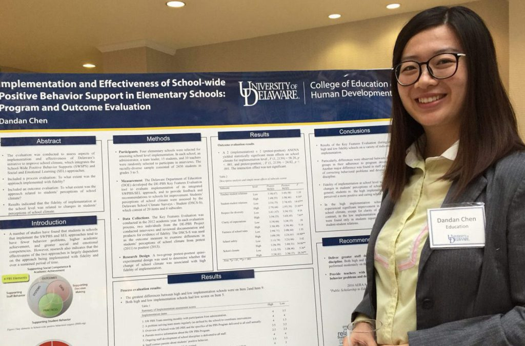 Graduate student Dandan Chen stands next to her research poster