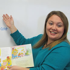 Erin Yetter poses in front of a whiteboard and holds a book