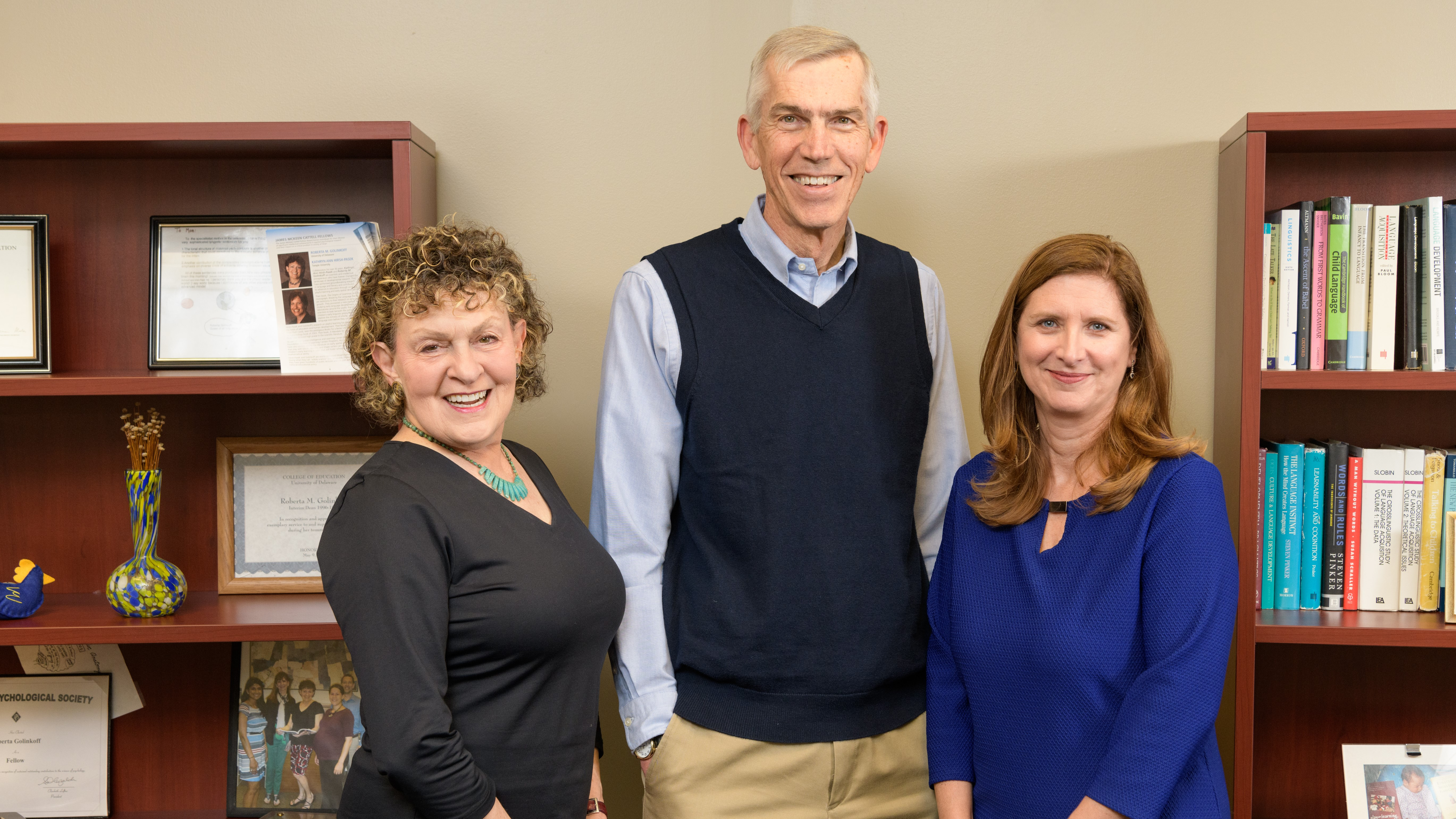 Three University of Delaware School of Education professors are 2019 AERA Fellows. From left to right: Roberta Golinkoff, James Hiebert, and Laura Desimone. They stand in front of bookshelves in one of their UD offices.