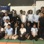 An elementary class at Warner Elementary poses for a group photo with a community police officer.