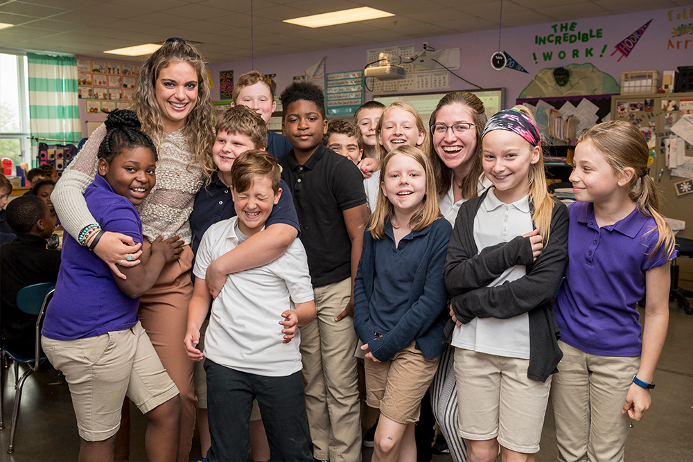 Two student teachers hug children in a classroom