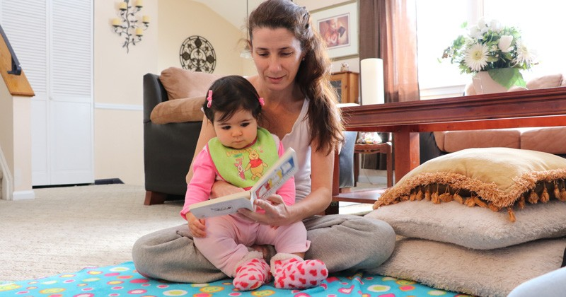 A mother enjoying quality time reading to her infant.