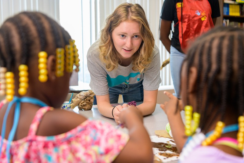 """UD student Ashley Warokomski shows students at West End Neighborhood House how to make """"slime"""" using glue, glitter and other materials, as they experiment with how varying the ratio of ingredients changes the result."""